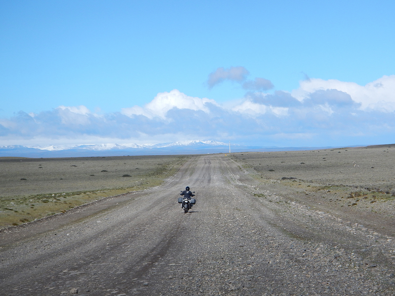 Dirt road in Argentina with snow capped mountains in the distance