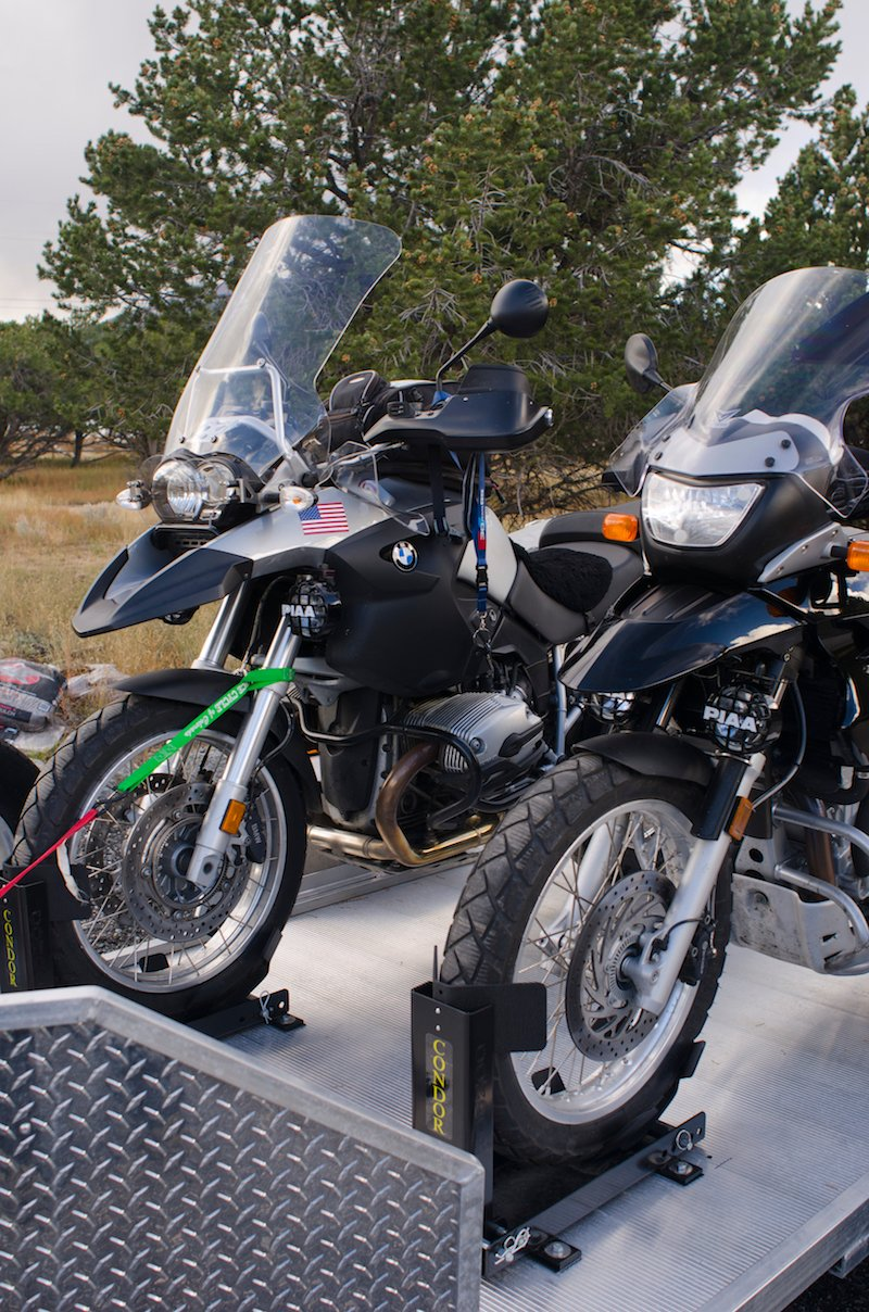 Two BMW motorcycles are loaded and tied down on a brand new trailer