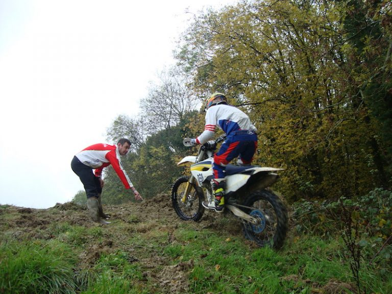 An instructor shows a rider how to ride a motorcycle up a steep slope