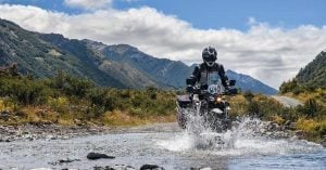 A motorcyclist crossing a river