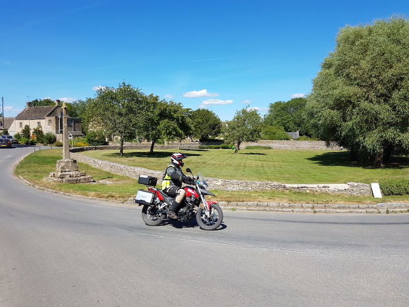 A 125cc motorcycle riding through a cotswold villiage