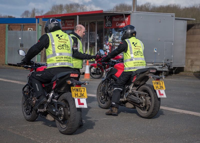 Two learners getting instruction to pass their motorcycle test