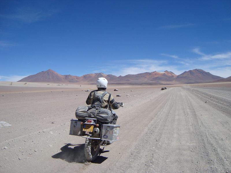 an adventure bike rider riding across the desert