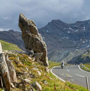 alpine passes motocylist large rock