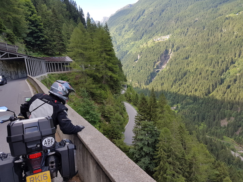 A Motorcyclist looks over a protective barrier on the splugen pass