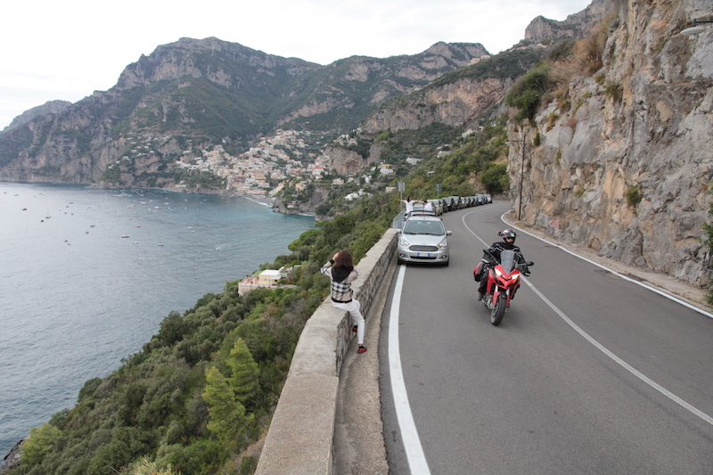 A red Ducati Multistrada and a tourist on the Amalfi Coast