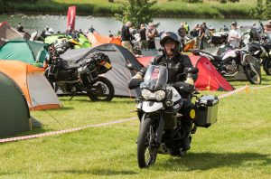 Man riding a Triumph Tiger while camping at the Adventure Bike Rider Festival