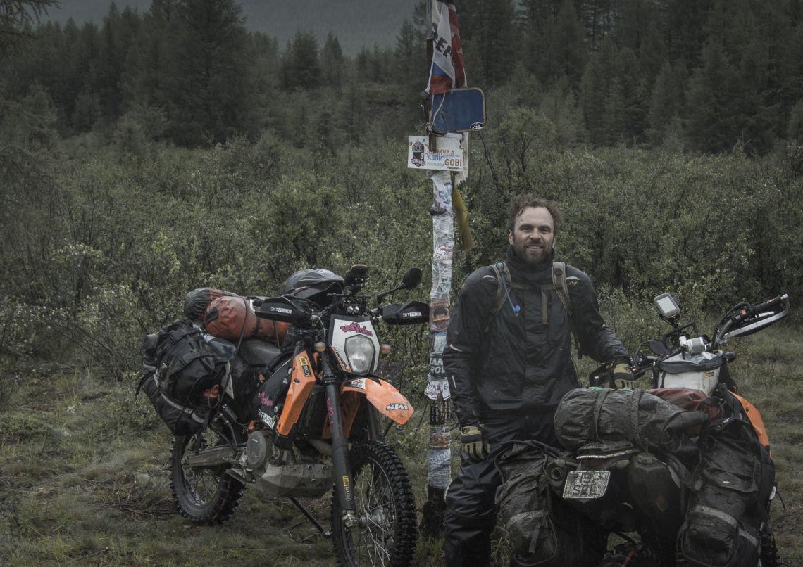 Jussi stood next to the 110 kilometre marker
